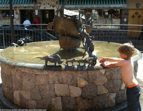 fun and funny photos of a child playing in a fountain in the Dolomites