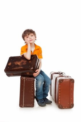 Boy sitting with pile of luggage wondering about the size of his oversized carryon