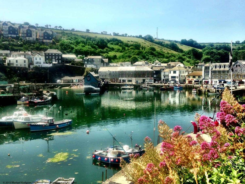 Mevagissey Harbor view with colorful boats and flowers.