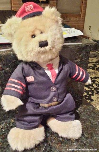 Dieter, one of the leaders of our family of traveling stuffed animals, making sure his uniform look spiffy for a day of being a conductor at Teddy & Friends: Perfect travel buddies