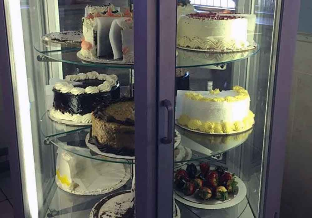 The diner tour as our band drools in front of a rack of cakes.