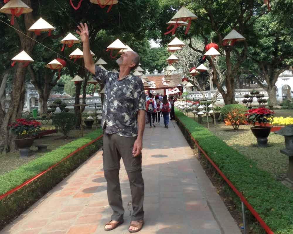 Jerry find is very hard to resist touching the hanging hats in Halong Bay in between our cruise ship boarding adventure.