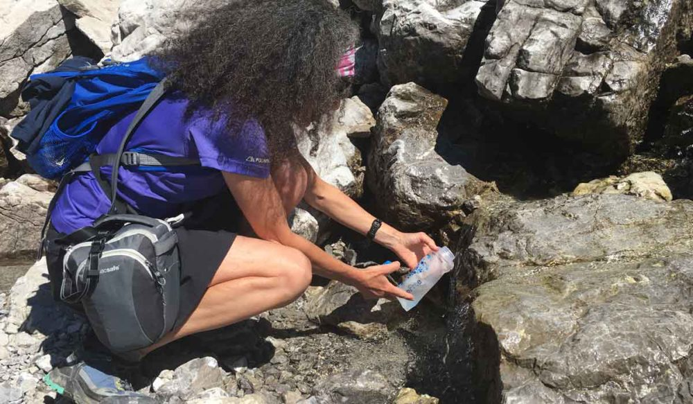 Therese using the Katadyn BeFree water filter to get water from a stream.