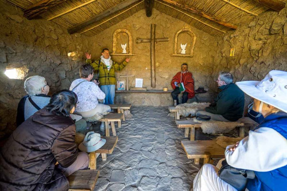 The guide (left) and village chief (right) explains how the roaming priest travels from village to village. This photo is inside the village's church.