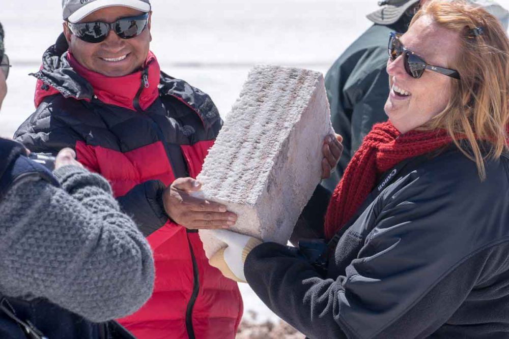 Journeys International staff, Lené, holds a salt block while visiting the salt flats.