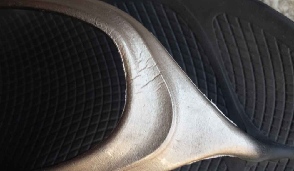 Oofos sandals show hairline cracks after compressing in luggage.