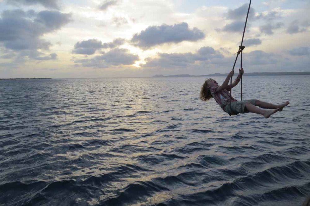 Enjoying fun on a rope swing with Family Dive Adventures in Bonaire.