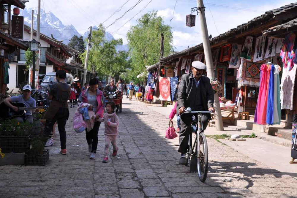 Baisha village street with a mountainous backdrop.