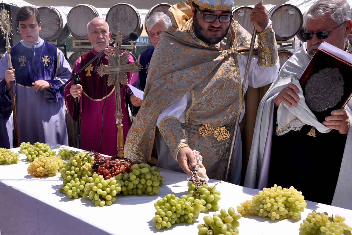 Der Hayr touches cross to grapes in blessing ceremony.