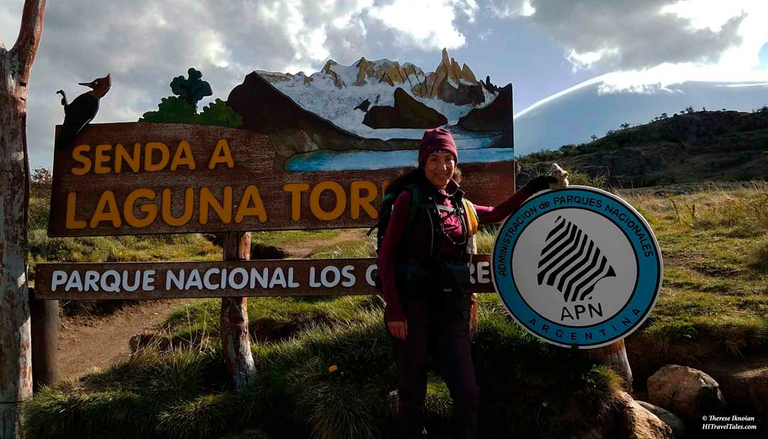 Standing beside the park sign for Laguna Torre in Patagonia.