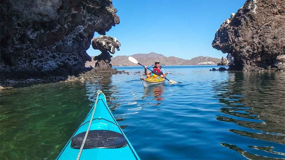 Jim Thomsen paddling a kayak behind Katie Thomsen