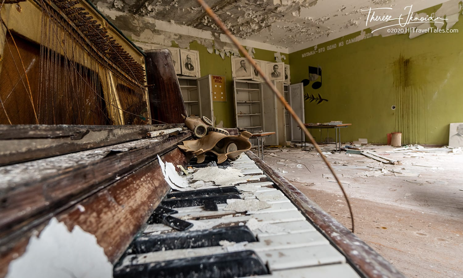A school's music room with a gas mask on a crumbling piano. The gas masks found here and there when visiting Chernobyl today are more than likely placed by tourists for photo ops or by unethical guides.