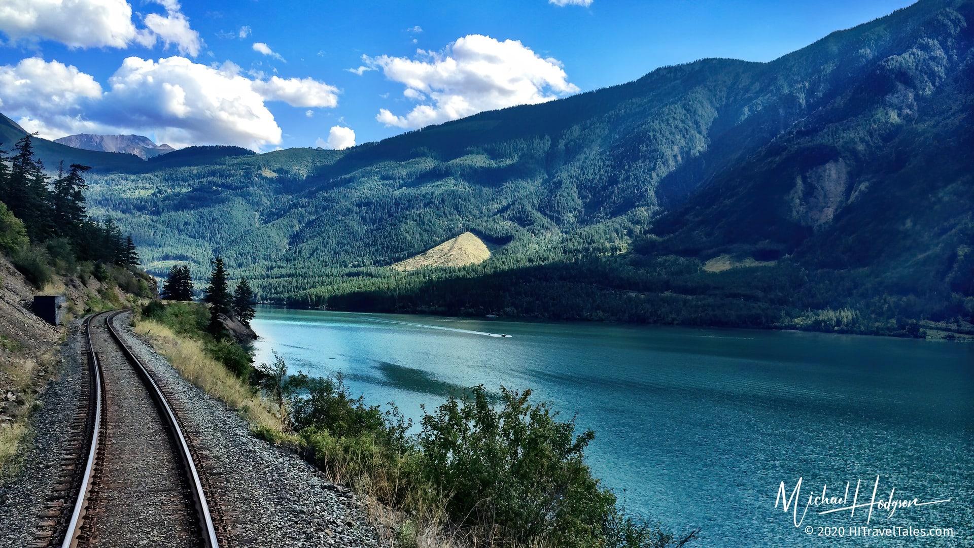 Train Tracks Alongside Water On A Rocky Mountaineer Luxury Train