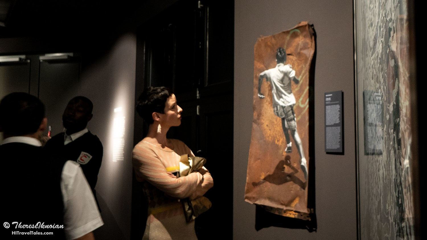 At the grand reopening of Urban Nation, a woman eyes a piece of art in one of the exhibit halls.