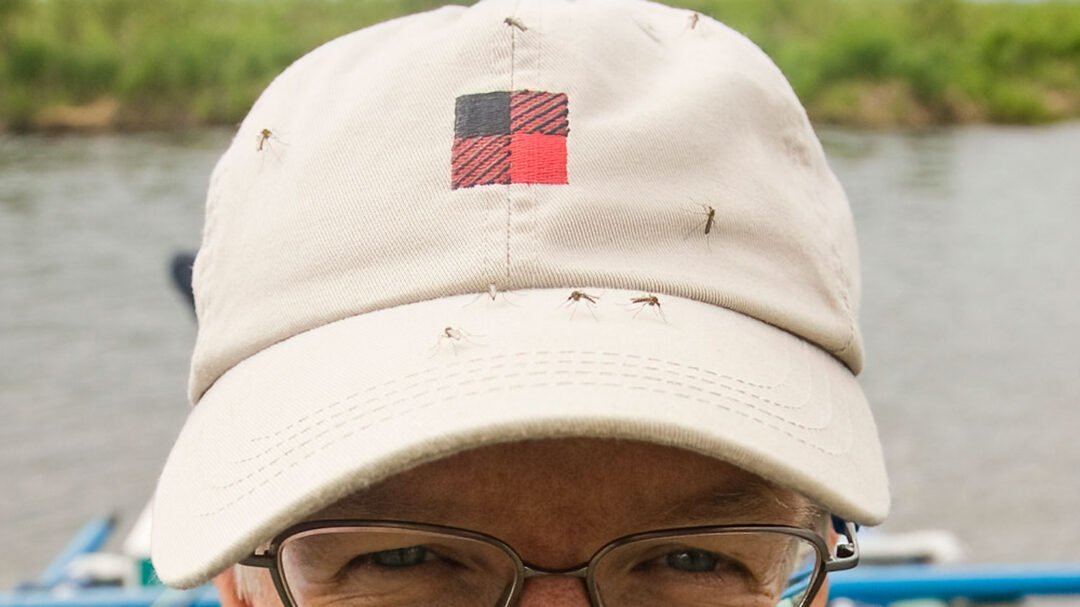 Mosquitoes Swarm on Michael's Hat in Alaska. He needs to find out what the best bug repellents are.